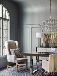 Dramatic, dark gray walls create a striking statement in the dining room, where an Aerin crystal chandelier glitters above a dining table and Bernhardt chairs.