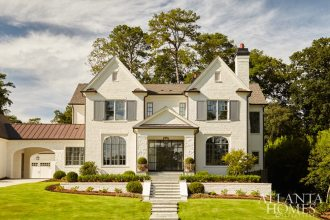 """Stanton suggested the Buskos paint the home's exterior (limestone included) a soothing white. Stanton also replaced the original front door with floor-to-ceiling metal windows. """"The house just glows, and the front door is such a statement,"""" he says."""