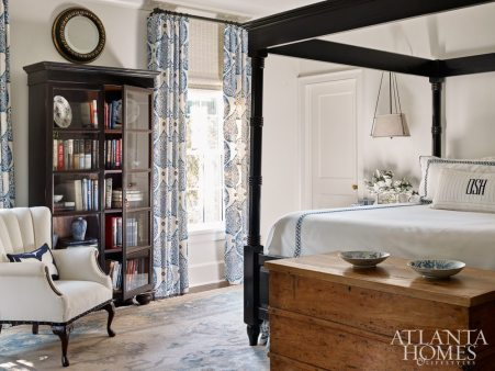 In the master bedroom, window treatments made with Galbraith & Paul fabric mingle with a reproduction Oushak rug, a British Colonial bookcase, a heirloom blanket chest and a few pieces of blue-and-white china.