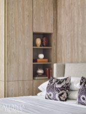 Wheeler concealed support columns with wood panels that create an elegant U-shaped niche for the bed. In lieu of nightstands, open shelving features outlets for electronics to control lighting and music. Cabinetry fabricated by California Closets.