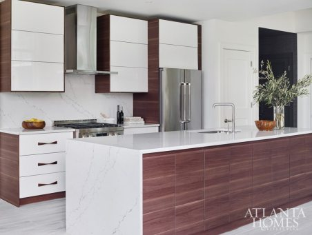 The two-tone kitchen features a durable modern quartz, while walnut adds warmth and cohesion with the home's antique wooden furnishings. To maximize storage, the new island was designed with push cabinets in the front. The cabinetry was fabricated by Royal Custom Cabinets.