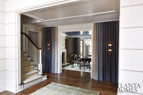 """The dining room is framed by ombré drapery panels that shift from natural linen to indigo. The room illustrates Musso Design Group's deft hand for mixing traditional and contemporary elements, with silver-leaf consoles, a vintage chandelier, antiqued mirrors etched by artisan Amy Smith in a Rothko-like pattern, a silk mural wallcovering from Armani Casa and a dining room table that was brought down from the homeowners' Maryland house. """"It's a bit of everything old, new, borrowed and blue,"""" says Musso."""