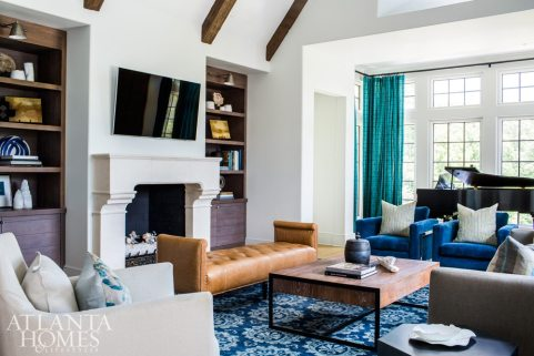 Natural light pours through the great room's ample windows, so McFadden determined strong color was in order. The bold blue rug inspired the scheme, which includes cobalt velvet armchairs and a rich leather bench placed in front of the limestone fireplace.