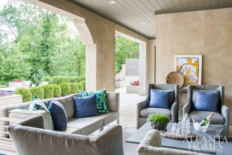 The outdoor room provides transition from the lower level to the pool and entertaining areas. McFadden filled it with slipcovered swivel chairs from Lee Industries and a sofa with pillows in a Janus et Cie fabric.