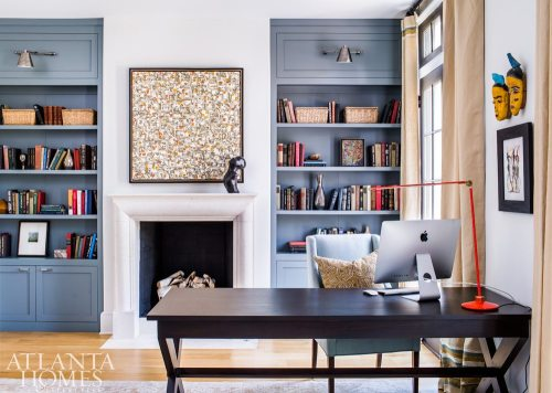 """Benjamin Moore's Templeton Gray makes the built-in bookcases stand out in the library. """"It actually takes on a more blue cast with the light in this room,"""" says McFadden. A contemporary painting and a bronze sculpture bring liveliness to the limestone fireplace."""