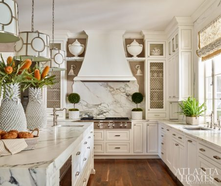 "The kitchen was the starting point for the project and, by the end, also its piece de resistance. Massive slabs of Calacatta Borghini white marble make an impact on the island and backsplash wall, while custom cabinetry—including an elegant vent hood—by Vickie Edwards of Kitchen & Bath Images brings exquisite craftsmanship to the ceiling. Savage selected accent pieces, such as the vintage ceramic pineapple centerpieces, with impact in mind. The mesh cabinet fronts were custom made in England, the woven-leather counter stools are Powell & Bonnell from R Hughes and the Roman shade fabric is Carleton V Ltd.'s Chateau in Gesso. ""The kitchen window opens onto the back porch, so you can serve drinks from the kitchen sink,"" says Savage."