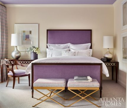 "Across from her younger sister's sleeping quarters, and featuring the same coordinating leopard-print carpet from Stark, the eldest daughter's refined bedroom features a Hickory Chair bed upholstered in plush amethyst silk velvet from Romo. It is punctuated by a pair of Suzanne Kasler's ""Lille"" X-benches for Hickory Chair to add a touch of glamour. The drapery fabric is from Jean de Merry, available through R Hughes."