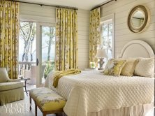 A charming chartreuse Nina Campbell fabric covered with beautiful blooms graces the master bedroom while the shiplap walls bring a casual note to the space.