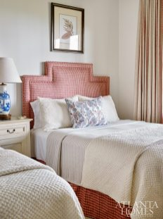 The lower level contains three guest-ready bedrooms, including this cozy beauty, where an angled upholstered headboard is tempered with feminine pillows and a blue-and-white porcelain lamp.