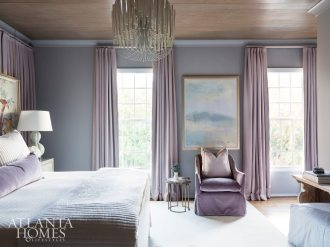 In this guest suite which is painted Sherwin-Williams Proper Gray, a wall of drapery panels hides unusable windows and absorbs noise to create a calming retreat. In front of the panels, artwork is suspended from the ceiling by brass chains. Purple hues abound in a plush chair from LEE Industries and drapery fabric through Pindler. The chandelier is through Arteriors.