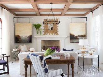 In the main living room, a cypress coffered beam ceiling provides warmth and texture. Russ wanted the space to feel comfortable yet orderly, so Turner used a pair of landscape paintings by Charlotte Terrell to conceal the room's television, while pops of plum reference the homeowners' family name. Mirror through Design Legacy. Sofa and desk chair through LEE Industries. Desk through Noir. The chandelier is through Currey & Company.