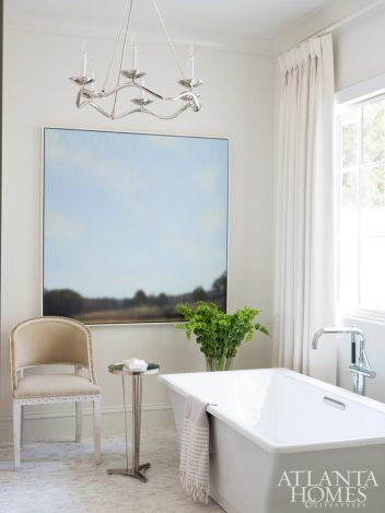The master bath is a calming oasis of neutrals; artwork from the Plumbs' personal collection and a chair from Mr. Brown rest beside a luxurious square tub from Kohler.