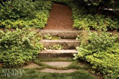 Low-growing saxifrage, variegated Solomon's seal and pachysandra are at the base of the secret garden path, which employs large pieces of slate as stepping stones.