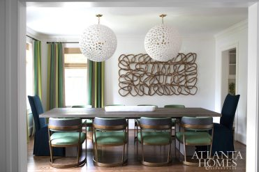 Skirted host and hostess chairs in a navy cotton anchor Kleinhelter's contemporary take on the dining room, where eight metal dining chairs are covered in a glazed-look Romo linen.