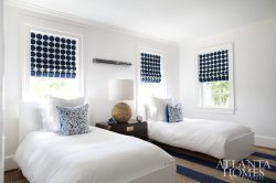In the boys' bedroom, a natural-fiber rug with bold blue stripes adds interest beneath a pair of twin beds and a classic campaign chest, while an oversize ball lamp, roman shades in a circle motif and patterned paper on the ceiling keep the room feeling youthful and fun.