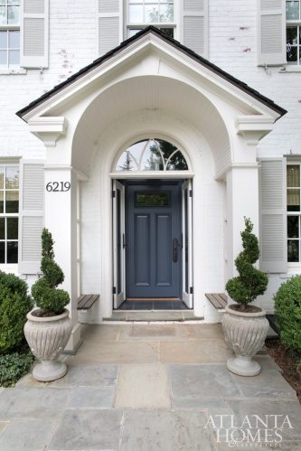 The color story starts at the entry, where boxwood topiaries flank a front door painted a rich Prussian blue, bringing fresh contrast to the traditional portico and painted brick.
