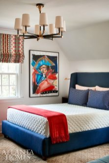 In the son's bedroom, bolder color choices spring from a Steve Penley painting of Napoleon. The bed is Mitchell Gold + Bob Williams upholstered in a navy linen by Schumacher.
