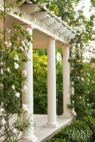 Roses climb a covered gazebo area off the guest house. opposite Graceful original details of the Neel Reid English Regency style home include a metal awning and a palladian window above.