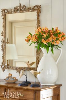 A mirror from Foxglove Antiques reflects a trio of bird accessories from Joseph Konrad.