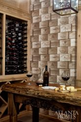 """The wine cellar provides an intimate space for the couple to entertain, while detailed stonework and steel doors help showcase their collection. """"As wine enthusiasts, we love to entertain, especially with our large family during holidays and on special occasions,"""" says Teresa. The wooden table was handmade by Allen, who picked up woodworking upon retirement. Edwards custom monogrammed the dining chairs with the Hughes' initials."""