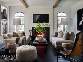 """Perfectly Proportioned The shiplap-framed living room's inviting seating group is composed of lofty Belgian-linen sofas aligned to a pair of weathered wood beams on the ceiling, while ancillary seating includes a leather sling chair and a T-shaped accent chair with nailhead details. The left wall bears bold images of a lion and a tiger from National Geographic; the """"art"""" over the mantel is actually Samsung's 4K Frame TV, which displays a series of art images when it senses movement; and a Todd Murphy piece is pictured at right."""