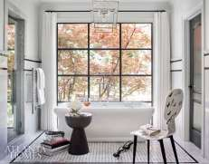 """Sitting demurely atop a tile """"rug,"""" MTI's freestanding tub affords a view of the Japanese maple in the backyard through a 12-paned metal window, and creates a dreamlike escape. A Fornasetti chair featuring butterflies is the perfect perch for personal effects. The vanity hardware, not shown, was gifted by R. Hughes."""