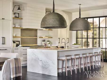 The open-format kitchen by Design Galleria Kitchen and Bath Studio features shiplap paneling, an integrated vent hood, integrated refrigeration, open shelves and brass bands that enhance the room's clean, horizontal lines. Oversize basket pendants preside over a marble-clad island with a waterfall edge. Appliances, Guy Gunter Home. Luxury hardware, Matthew Quinn Collection.