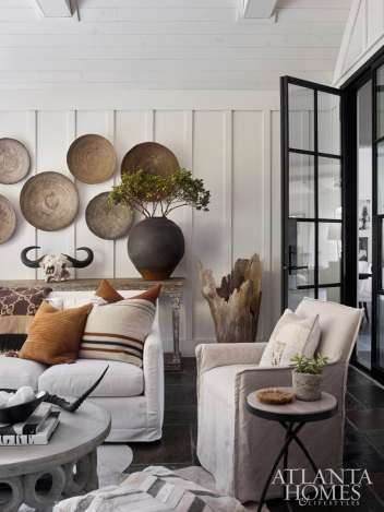 Connected to the kitchen by floor-to-ceiling, wall-to-wall bifold steel doors is the screened porch, where a collection of woven baskets decorates a wainscoted wall.