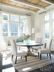 A curved bench and slipcovered chairs add comfort to the dining area of this Florida beach home, designed by Suzanne Kasler, while a rustic table and handmade rug from Afghanistan add texture.