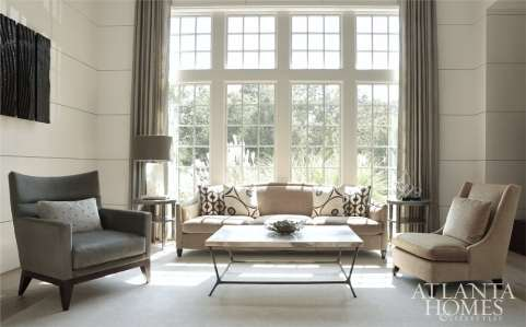 Fronting a bank of double-height windows, one of the formal living room's seating groups illustrates the home's generous dimensions. One of Mills Kirk's selenite-base Studio B5B Collection table lamps punctuates the arrangement.
