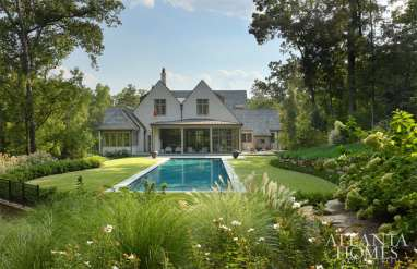 """The landscape architect for the project was Eric King, whom Mills Kirk lauds heartily: """"We talk so much about bringing the outside in; he's great at bringing the inside out."""" The pair of pots flanking the pool are from Chip and Company."""