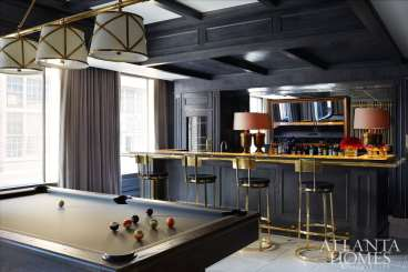 "The home's overall lighthearted look takes a turn in the bar and billiards space with an illuminated onyx bar top. ""It's a nighttime room, so we used a dark gray for the bar area,"" says Turner. An antique mirror and shapely lamps temper the room's masculine feel."
