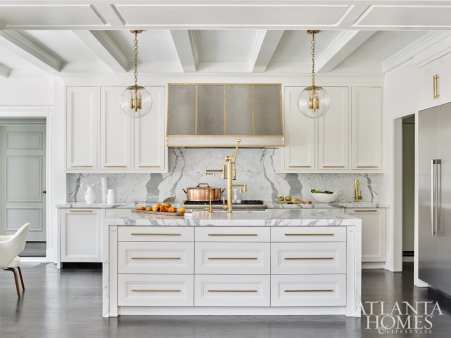 The kitchen cabinetry is by Kingdom Woodworks. Gleaming fixtures, such as Waterstone faucets and Emteck hardware, temper the marble accents fabricated by Marmi Natural Stone. Pot, Foxglove Antiques.