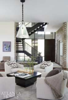 A pendant by Mattaliano illuminates a quartet of swivel chairs with rounded backs gathered around a square cocktail table from Baker Furniture in the great room.