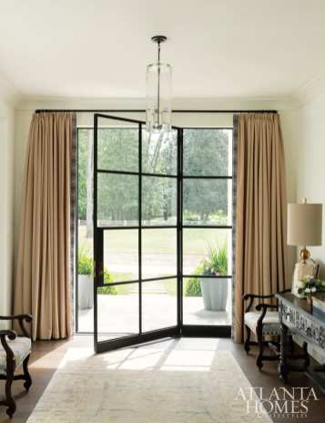 Bradley softened the steel-and-glass front entry with latte-toned drapery panels. The drapery fabric is by Mokum, through Paul+, and the trim is Samuel & Sons trim. The Pendant is from South of Market, the table lamp is Noir, and the Oushak rug is Designer Carpets.