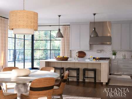 In the farmhouse-inspired kitchen, a trio of Palecek counter stools sidles up to an island anchored by bleached white oak, while stainless steel accents—a simple hood and a pair of coordinating pendants (Circa Lighting's Fulton style in Industrial Steel)—offer a utilitarian feel. The floral fabric used for the drapery panels is a Kerry Joyce design, and the natural-fiber pendant over the breakfast table is the Amani Drum from Made Goods.