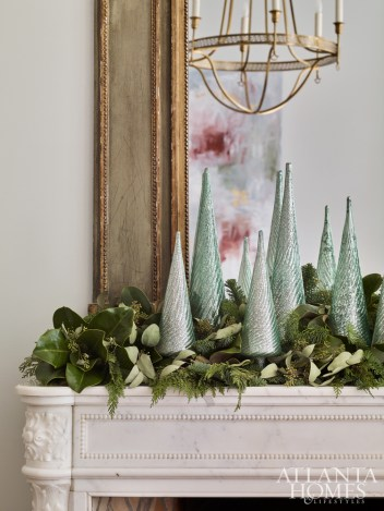 The marble mantel is deep enough for holiday greenery, by Floralis Garden Design, and glittery decorative trees.