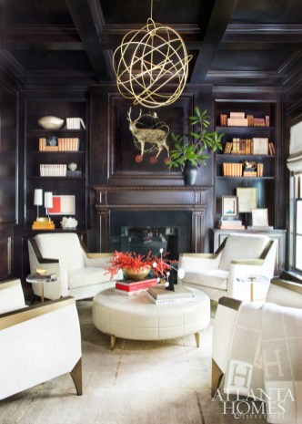 Wood and antiqued bronze Jean De Merry chairs, covered in a cream Nancy Corzine fabric, invite conversations in the ebony- paneled library.