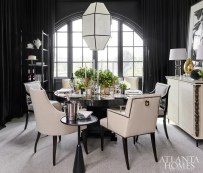 The black-and-white dining room blends vintage mid-century modern pieces, such as the lantern and sideboard, with newer pieces, such as the lacquered dining table, abstract art and brass and bronze sculptures.