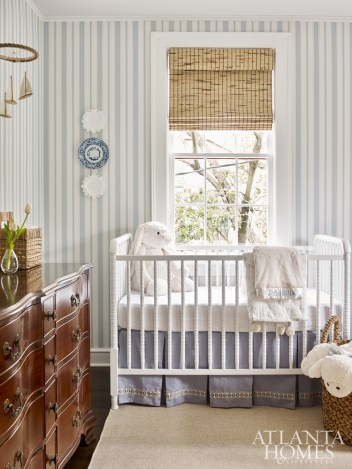 Brimming with charm, the nursery features wallpaper from Cole & Son. Like many of the home's vintage and antique pieces, the dresser once belonged to the house's previous owners. The chairs were purchased at Scott Antique Markets and the crib is from Wayfair. The crib skirt is custom. The fabric is from Ballard and the trim is Passementerie through Travis & Com