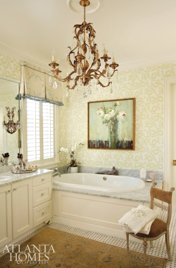 The master bath features a celadon-colored floral-print paper (Ardley in Sage by Peter Fasano) and a painting from Huff Harrington Fine Art. An antique Tabriz rug from John Overton grounds the room in softness, while Vaughan's Chambord chandelier and coordinating David Iatesta Marseille sconces lend it a formal, feminine flourish.