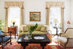 Floor-to-ceiling draperies frame a Brunschwig & Fils fabric-clad sofa. A collected feel is achieved with artwork from France and a menagerie of antique furnishings.