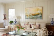 """A bird motif, seen on hand-painted pillows and skirted round table from Jerry Pair, lends color to the family room. An abstract work from Pryor Fine Art pops against a Lee Industries sofa and chairs recovered in oatmeal fabric to """"play second fiddle to the artwork and, really, the people,"""" says Jones."""