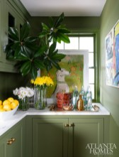 Green walls, moldings and cabinetry define the butler's pantry.