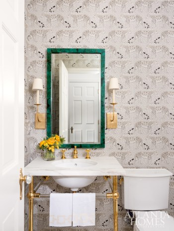 A green mirror stands out against a Cole & Son wallcovering.
