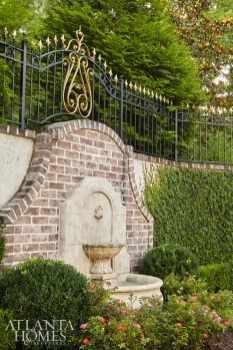 The Harrison Design team elevated the scale of the entry with two larger tiers topped with limestone ball finials that convey the home's ornamental and grandiose feel.