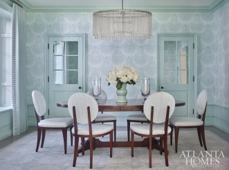 Farrow & Ball's Lotus wallpaper serves as the foundation for the bold yet understated dining room. Century Furniture dining chairs, upholstered in Downey by Christopher Farr Cloth, sidle up to a classic-meets-modern dining table by Mr. and Mrs. Howard for Sherrill Furniture. The chandelier is by Arteriors.
