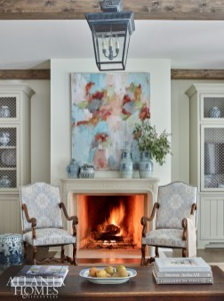 """Built-in bookcases with lattice detailing flank the limestone fireplace by Francois & Co., which is topped by a lively abstract painting. """"We wanted the family den to blend seamlessly with the look of the kitchen and breakfast room, so we used the same fabrics in soft neutral shades of blue and taupe,"""" says DeLoach."""