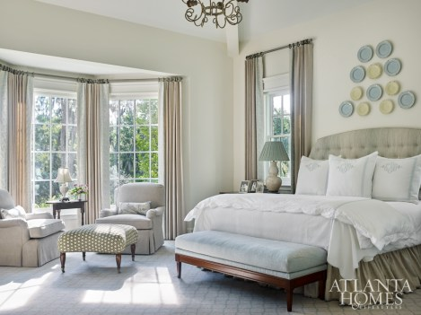 The palette of master bedroom was inspired by its coastal setting. The upholstered headboard is dressed in Travers fabric with bed linens from Leontine Linens. The Hickory Chair bench, covered in Richard Smith fabric, is the perfect height for the family dogs to reach the bed.