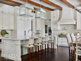 In the classic white kitchen, a pale blue painted island and lanterns from Paul Ferrante, also in blue, keep the soft palette flowing in the open floor plan. The Holland Macrae barstools are upholstered in a Richard Smith fabric.